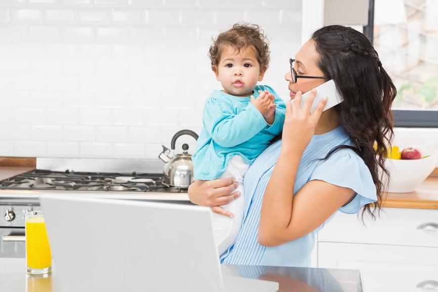Lächelnde Hebamme, welche ein Baby hält beim Telefonanruf in der Küche