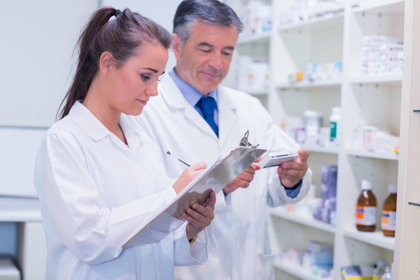 Apotheker/-in, die ein Medikament nach einer Verordnung in der Apotheke sucht.